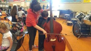A student helps another play bass.