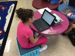 A student in Mrs. Izbicki's class is diligently reading the rubric provided to her in the iLearn writer's workshop module.