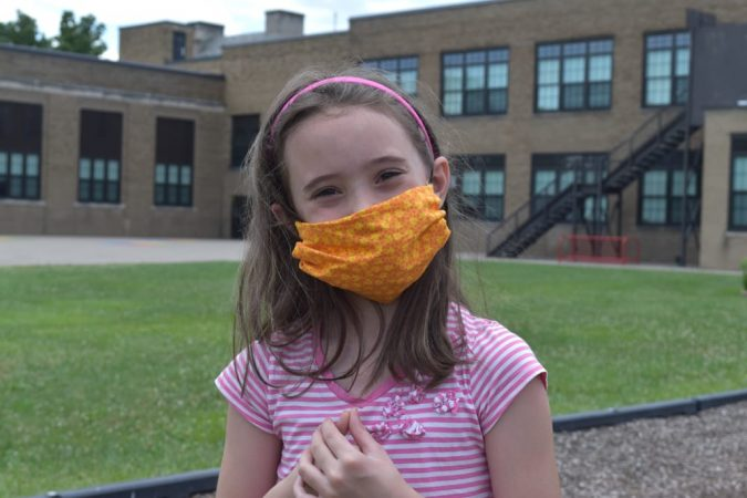 A girl in a face mask poses outside an elementary school.